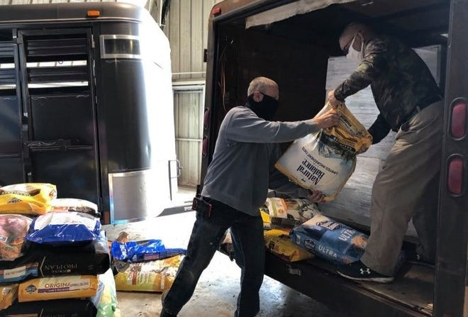 Marty Hager and Frank Miller unload bags of pet food donated to the animal shelter.