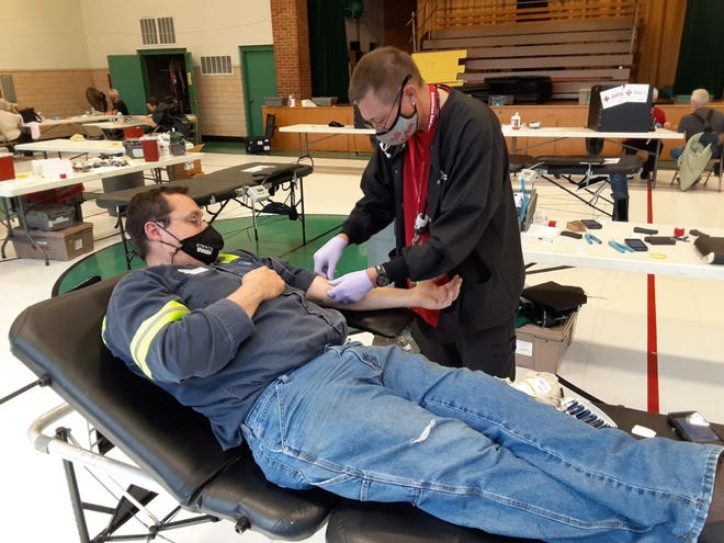 Ken Szych (right), a blood collection technician for the American Red Cross, preps the arm of Jim Shields from Erie at a blood drive held in the Zion Lutheran School gym in Monroe in the spring. Shields, 35, was one of about 35 persons who donated a pint of blood during the drive.