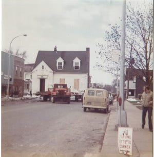 Von Thompson can be seen riding on top his new old house in 1973 along E. Main St. in Milan. They were headed for 157 County St. where the exploded house used to be.