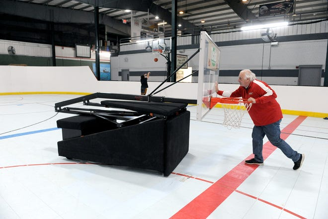 James Farrar pushes a basketball net out onto the floor of the Habitat for Sports center in Uxbridge, April 30, 2021. With the onset COVID-19, Farrar and his wife, Becky, are closing 'The Hab' later this month.