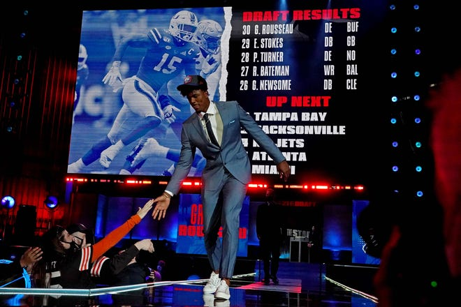 Former UM defensive end Gregory Rousseau walks on stage in Cleveland after being selected by the Buffalo Bills late in the first round of the NFL Draft Thursday night.
