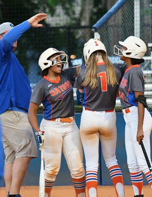 Palm Beach Gardens players Kairi Rodriguez, left, and Genesis Duran, right, celebrate teammate Brooke Bernard's two-run home run in the bottom of the fourth inning. The Gators went on to win Thursday's district finals with a 12-5 victory over Jupiter.