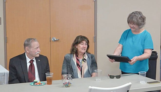 Jim Lakey, left, and his wife, Marlies, listen as Sandyland Shepherd's Center director Martha Cutright reads a certificate of appreciation that was presented to Lakey as a special retirement party in his honor earlier this month. Lakey served as Sandyland director for 26 years.
