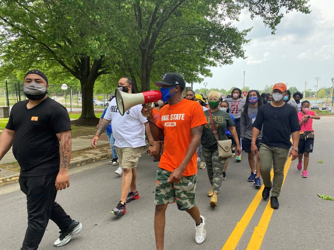 Jhovan Galberth, founder of MOVE at Virginia State University, leads the crowd in chants in support at a unity march.