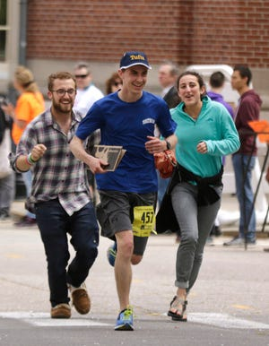 Robert Hrabchak is joined by friends for his final few hundred feet to the finish line of the Providence Marathon in 2017. The race returns this year, although smaller, after the in-person race was canceled last year and held virtually because of the coronavirus.