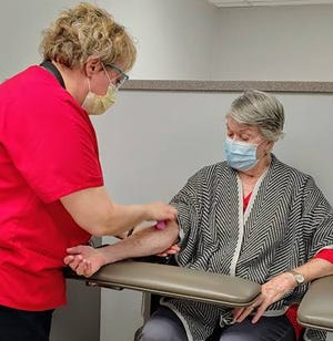 Phlebotomist Melissa Dotson helps a patient with testing at the new lab at University Hospitals Portage Medical Center.