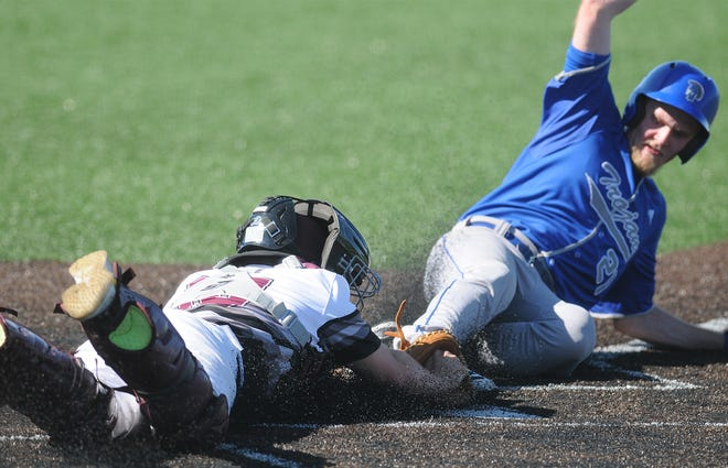 Salina Central's Brooks Richardson tries to tag Andover Trojan's Brandon Klusener (21) out at home plate during the third inning on Apr. 30 at Dean Evans Stadium.