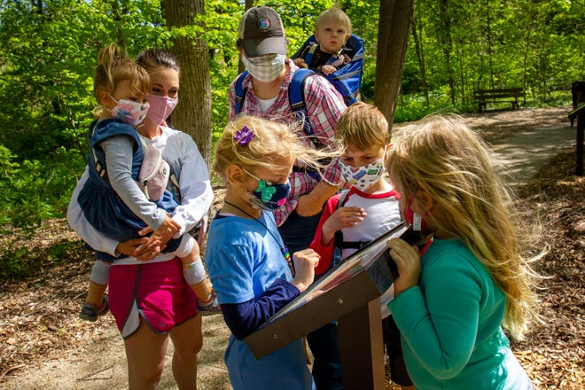 """From left, Ella Willey, 3, carried by her mother, Elizabeth Willey; Sara Mosher, 7; Sara's mother, Emily Mosher, carrying Caleb Mosher, 1, Ben Willey, 7, and Abigail Mosher, 4, stop to check out pages from """"Wangari's Trees of Peace: A True Story from Africa,"""" by Jeanette Winter, along the StoryWalk made possible by Lincoln Library and the National Endowment for the Arts Big Read: Sangamon County along a walking route Friday at Lincoln Memorial Garden in Springfield."""