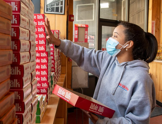 Seraphi Montero stocks shelves with Table Talk pies at the Pie Store on Green Street on Friday. Table Talk will give one free 4-inch snack pie to customers that present their COVID-19 vaccination card.