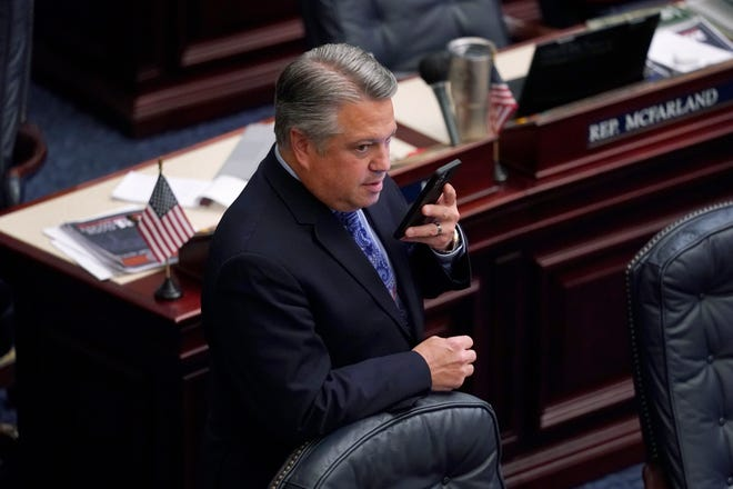Florida Rep. Chip LaMarca talks on his phone during a break in a legislative session Thursday at the Capitol in Tallahassee.