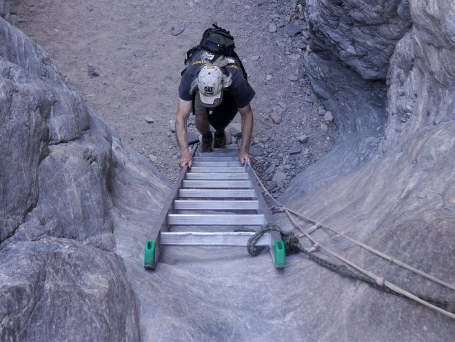 Paul climbs a ladder to the next part of the Ladder Canyon and Painted Canyon Trail near Mecca, Calif.