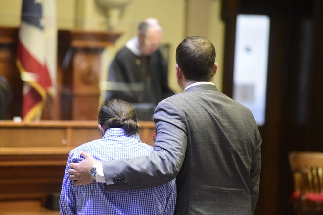Defense attorney Adam Stone places his arm around Joshua Benedict as visiting judge Howard Hall prepares to read the man's verdict Friday.