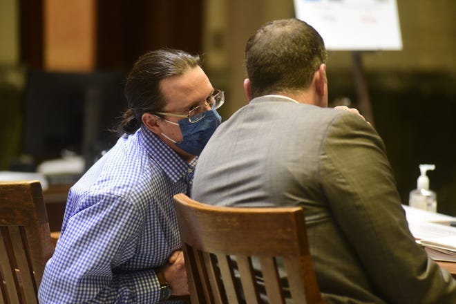 Joshua Benedict leans in to speak with Adam Stone, his defense attorney, during closing arguments in his trial on April 30.