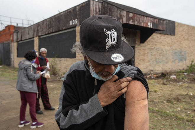 James Hatcher of Detroit holds his sleeve up while looking at a bandage on his arm after getting a Moderna COVID-19 vaccine from Central City Integrated Health nurses as he walked along Hamilton Avenue in Detroit on Wednesday, April 28, 2021. Central City Integrated Health paired up with The Salvation Army during their Bed & Bread Club delivery route delivering meals to Detroit residents to bring the COVID vaccine to those who might not have transportation to have access to the vaccine.
