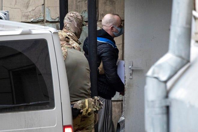 Ivan Safronov, kanan, mantan penasihat direktur perusahaan luar angkasa negara Rusia, masuk ke gedung pengadilan yang dikelilingi oleh petugas Layanan Keamanan Federal Rusia di Moskow, Rusia, Jumat, 30 April 2021. Pengacara yang berbasis di St. Petersburg Ivan Pavlov adalah juga membela Safronov dan dijadwalkan hadir di pengadilan Moskow pada hari Jumat pada sidang untuk memperpanjang penahanan pra-sidang Safronov.