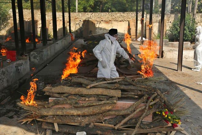 Seorang anggota keluarga melakukan ritual terakhir korban COVID-19 di krematorium di Jammu, di Jammu, India, Jumat, 30 April 2021.