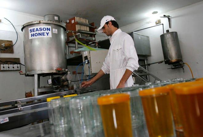 Dalam file foto 12 Mei 2009 ini, seorang pekerja mengisi toples dengan madu di sebuah perusahaan produksi yang didukung oleh Badan Pembangunan Internasional Amerika Serikat, di Jalalabad, Afghanistan.