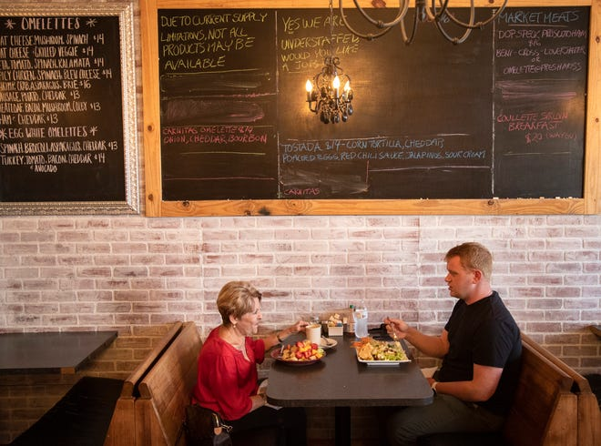 """Pam Jensen and her grandson Robert eat at Crave on Thursday, April 29, 2021, in Fort Myers. The restaurant, along with many others, is struggling to find enough servers and cooks to operate at full capacity. The chalkboard above them reads, """"Yes, we are understaffed. Would you like a job?"""""""
