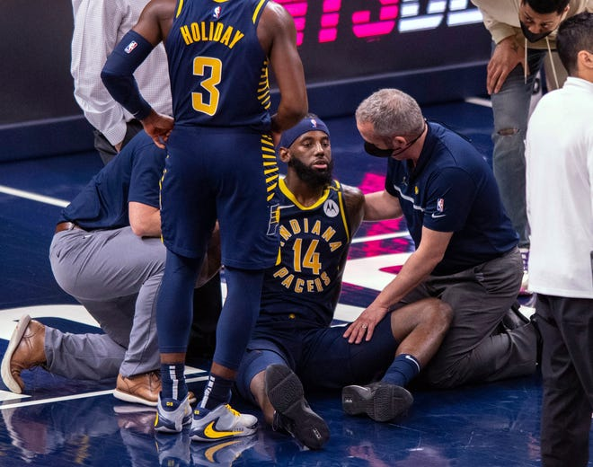 Indiana Pacers trainers check on the condition of forward JaKarr Sampson (14) after an apparent injury during the second half of the team's NBA basketball game against the Brooklyn Nets in Indianapolis, Thursday, April 29, 2021. (AP Photo/Doug McSchooler)
