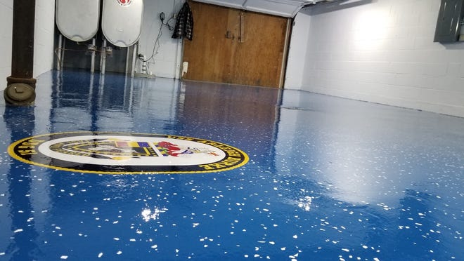 """A Colgate garage is shown after being redone by Garage Floors of Wisconsin. The color is """"Ford Blue"""" in epoxy paint and the insignia is for for the destroyer USS Arleigh Burke"""