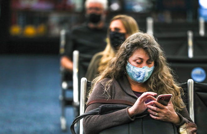 Sarah Riforgiate uses her cellphone to pass the time Thursday, April 29, 2021, at Milwaukee Mitchell International Airport in Milwaukee.