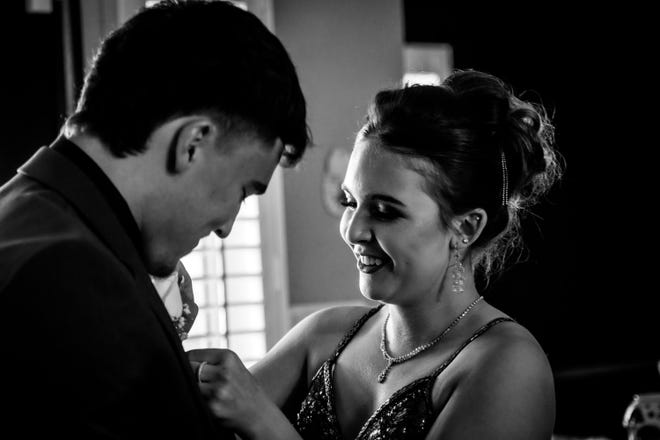 Miranda Romero, senior at Las Cruces High School, attaches a boutonniere onto her date, Marcos Lopez, senior and LCHS quarterback, before heading to her school's prom on April 24, 2021.