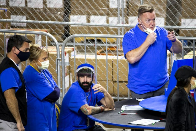 Former Arizona lawmaker Anthony Kern (right, standing) helps in examining and recounting Maricopa County ballots from the 2020 general election with contractors hired by the Arizona Senate at the Veterans Memorial Coliseum in Phoenix on April 30, 2021. Kern, who was on the 2020 general election ballot, also was in Washington, D.C., during the Jan. 6 Capitol riot.
