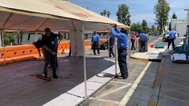 """Crews remove emergency-use tents outside Sierra View Medical Center's emergency department. The hospital is seeing an """"all-time"""" low number of COVID-19 cases."""