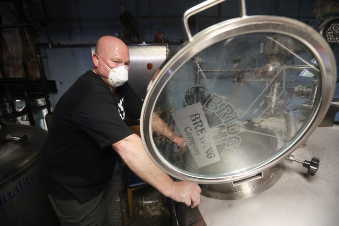 Ray Ballard watches as water and ground grains pour into a the brew tank at Y Bridge Brewing. After a career as a musician and a nurse, Ballard now owns and operates a brewery.