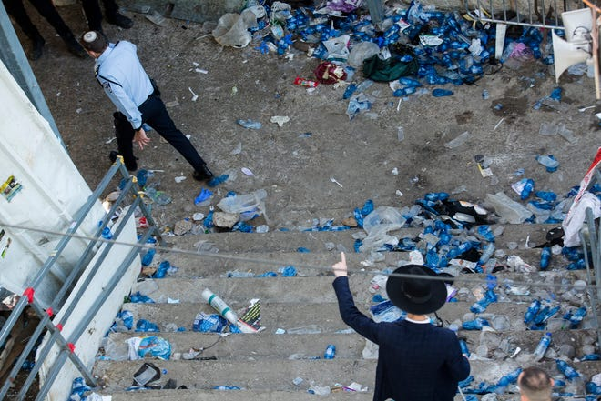 A police officer and an Ultra Orthodox Jewish man walk at the scene where dozens were killed in crush at a religious festival in Mount Meron on April 30, 2021 in Meron, Israel.