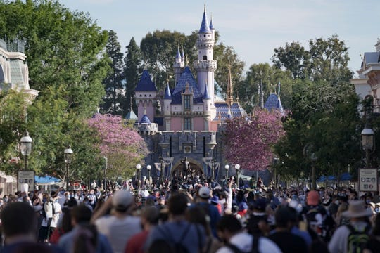 Ticket holders walk around Disneyland on the morning of Disneyland reopening to the public after closing for more than a year due to the ongoing pandemic.