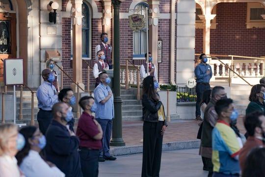 Disneyland Cast Members watch as Color Guard members raise the flag inside Disneyland.