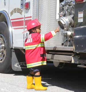 August Brown explores Cuyahoga Falls Fire Department truck during a stop at his Cuyahoga falls home Saturday for his third birthday.
