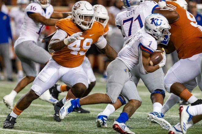 Texas defensive lineman Ta'Quon Graham (49) chases Kansas running back Pooka Williams Jr. (1) in Austin on Oct. 19, 2019.