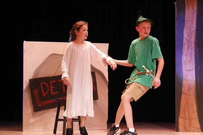 """Peter Pan, played by A.J. Tidwell, tries to pull Wendy, played by Brynlee McDermed, to safety after hearing pirates coming during a rehearsal of the play """"Pan!"""" at Early Elementary School Friday afternoon. The play is being performed by a nine-member cast of fifth-graders."""