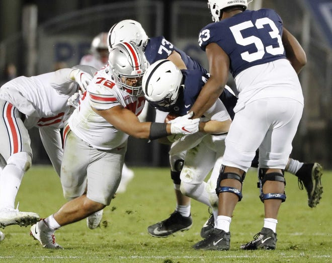 Ohio State defensive tackle Tommy Togiai sacks Penn State quarterback Sean Clifford, one of three sacks he had in the game.
