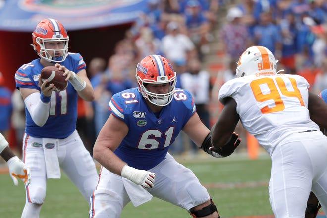 Florida offensive lineman Brett Heggie (61) blocks for quarterback Kyle Trask (11) against Tennessee defensive lineman Matthew Butler (94) during a game in 2019 in Gainesville. [JOHN RAOUX / AP]