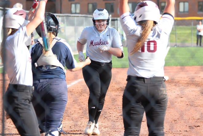 John Glenn freshman Sydney Marshall (18) is greeted a home plate by her team mates after slugging a two-run home run in the fourth inning  Friday against Morgan in the Lady Muskies 9-0 win. The Lady Muskies improved to a perfect 24-0 with the lopsided victory