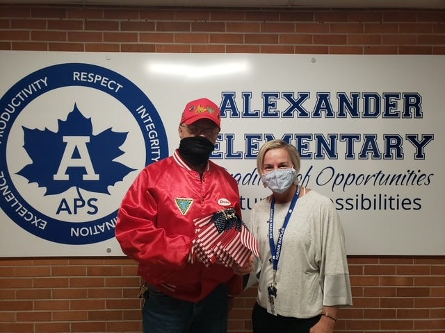 Dave Loop, Americanism director for the 40 & 8 of Lenawee County, is pictured dropping off several American flags to Alexander Elementary School Principal Shanan Henline in Adrian.