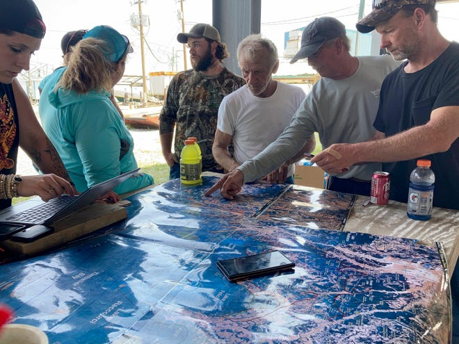 Volunteers gather around a map of the Louisiana coast Thursday, April 30, 2021, in Cocodrie as they search for survivors of the Seacor Power, an oilfield liftboat that capsized in a storm April 13 about eight miles south of Port Fourchon.