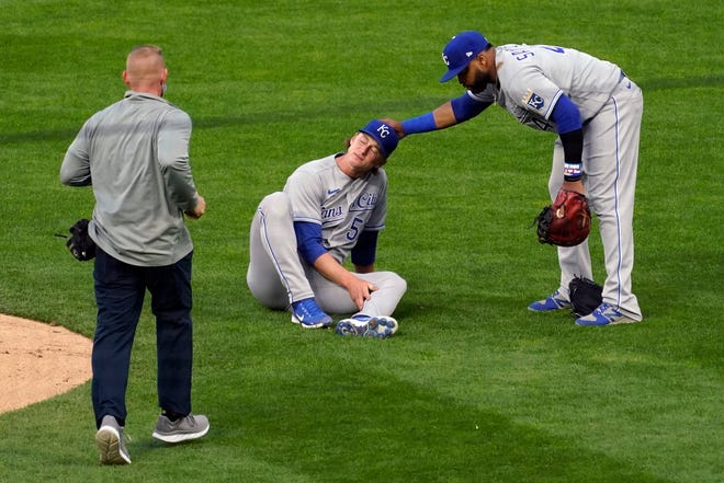 Kansas City Royals pitcher Brady Singer, center, is consoled by first baseman Carlos Santana as he holds his leg after a line drive hit him during the second inning of Friday's game against the Minnesota Twins. Singer left the game and the Royals suffered a 9-1 loss.
