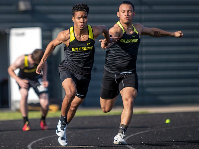 Galesburg's Orlando Ferguson, left, takes the baton from fellow senior Kyron Leath during the 4x100 meter relay at the Silver Streaks' triangular meet with Rock Island and Sterling on Friday, April 30, 2021 at Van Dyke Field.