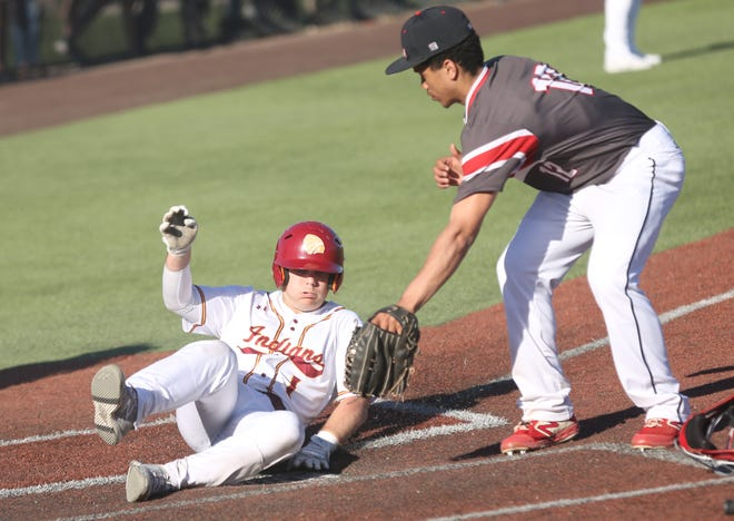 Hays High's Dalton Dale slides home safely during the second game against Liberal on Friday at Hays High.
