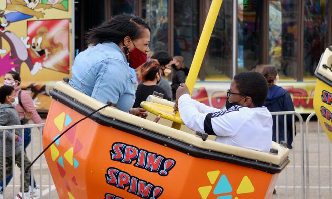 Patrina and Brian Vermillion of Spring Lake hang on for a twirl on the Spin, Spin, Spin ride Saturday, May 1, 2021, at the Tulip Time festival at the Holland Civic Center.