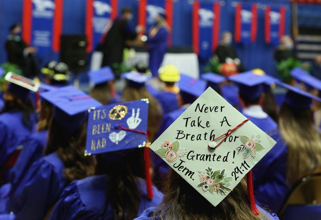 MacKenzie MacMahon watches as students are given their diplomas while wearing her decorated graduation cap at the Hutchinson Community College commencement ceremony Friday at the Sports Arena.