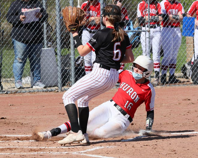 New Boston Huron's Alexis Thomas (16) slides home while Clinton's Kendall Phillip covers the base during Friday's doubleheader in Clinton.