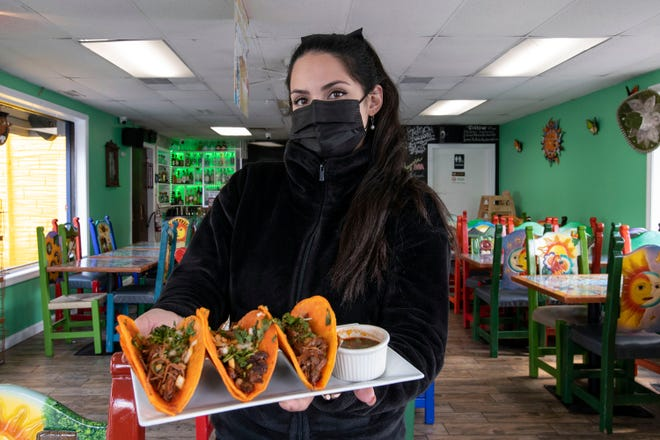 Aztec Restaurant co-owner Dulce Guerrero holds Birria tacos with a cup of consomé for dipping, at the Waverly Street restaurant on Friday.