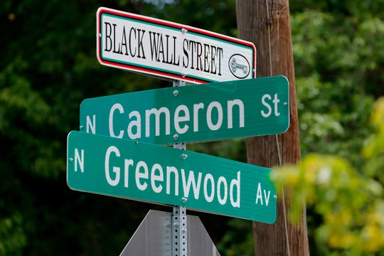 Street signs in the historic Greenwood District in North Tulsa, known at the time as Black Wall Street, the site of a massacre of African Americans by a white mob, resulting in hundreds of deaths in 1921. Seen in Tulsa on Friday, June 12, 2020. [Doug Hoke/The Oklahoman]