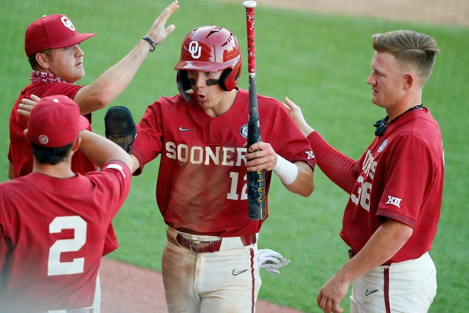 Oklahoma's Brett Squires (12) celebrates with Trent Brown (2) and Tyler Hardman (36) after scoring a run against Oklahoma State at O'Brate Stadium in April.