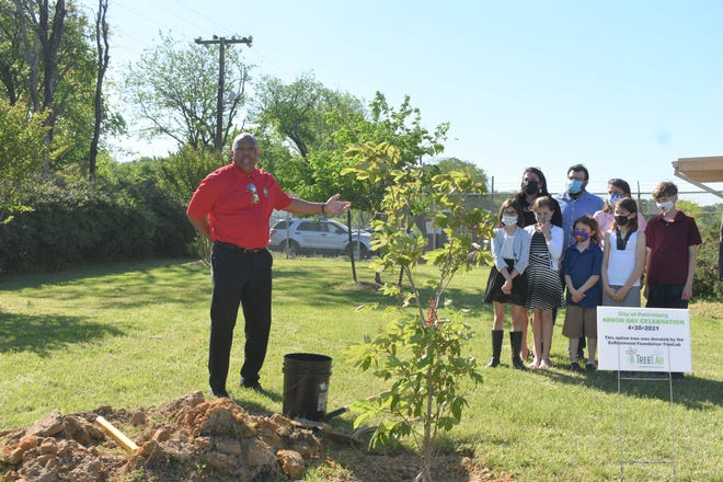 Deputy City Manager Lionel Lyons speaks at a tree planting ceremony honoring the recently passed Director of Neighborhood Services Frank Poulin. His two sisters, their husbands and children stand nearby.
